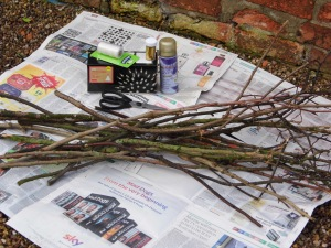 You will need: 15 dry sticks, newspaper, string, scissors, gold spray paint, gold glitter, string of 100 fairy lights