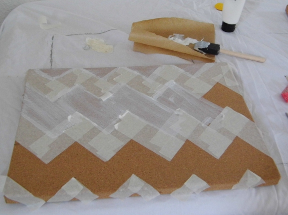 Take a plain cork board and create a stencil using masking tape. Once I had created the top chevron I measured the distance between the points in order to make the next row. Paint the areas in between the masking tape.