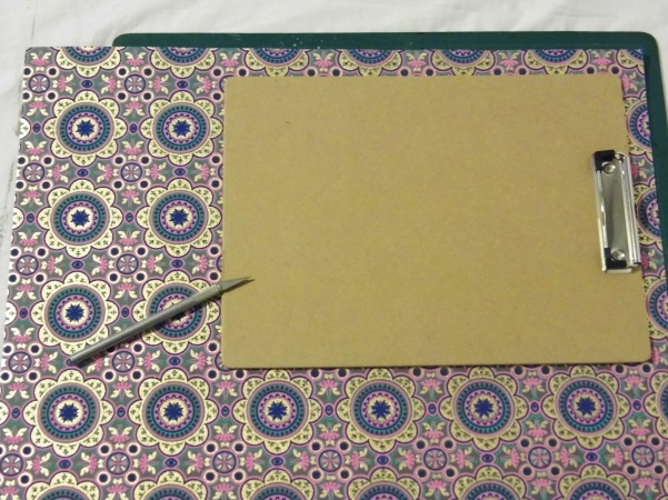 Place it on top of your decorative paper. Using your craft knife and cutting board, cut around the outline of the board.